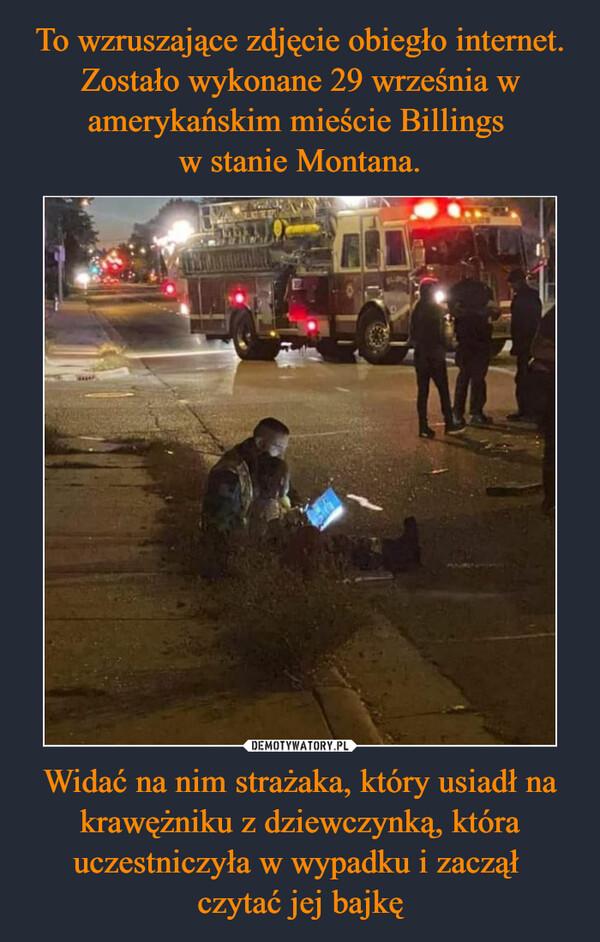 Widać na nim strażaka, który usiadł na krawężniku z dziewczynką, która uczestniczyła w wypadku i zaczął czytać jej bajkę –